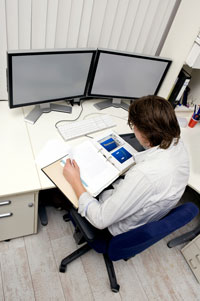 Man in front of a dual-display computer